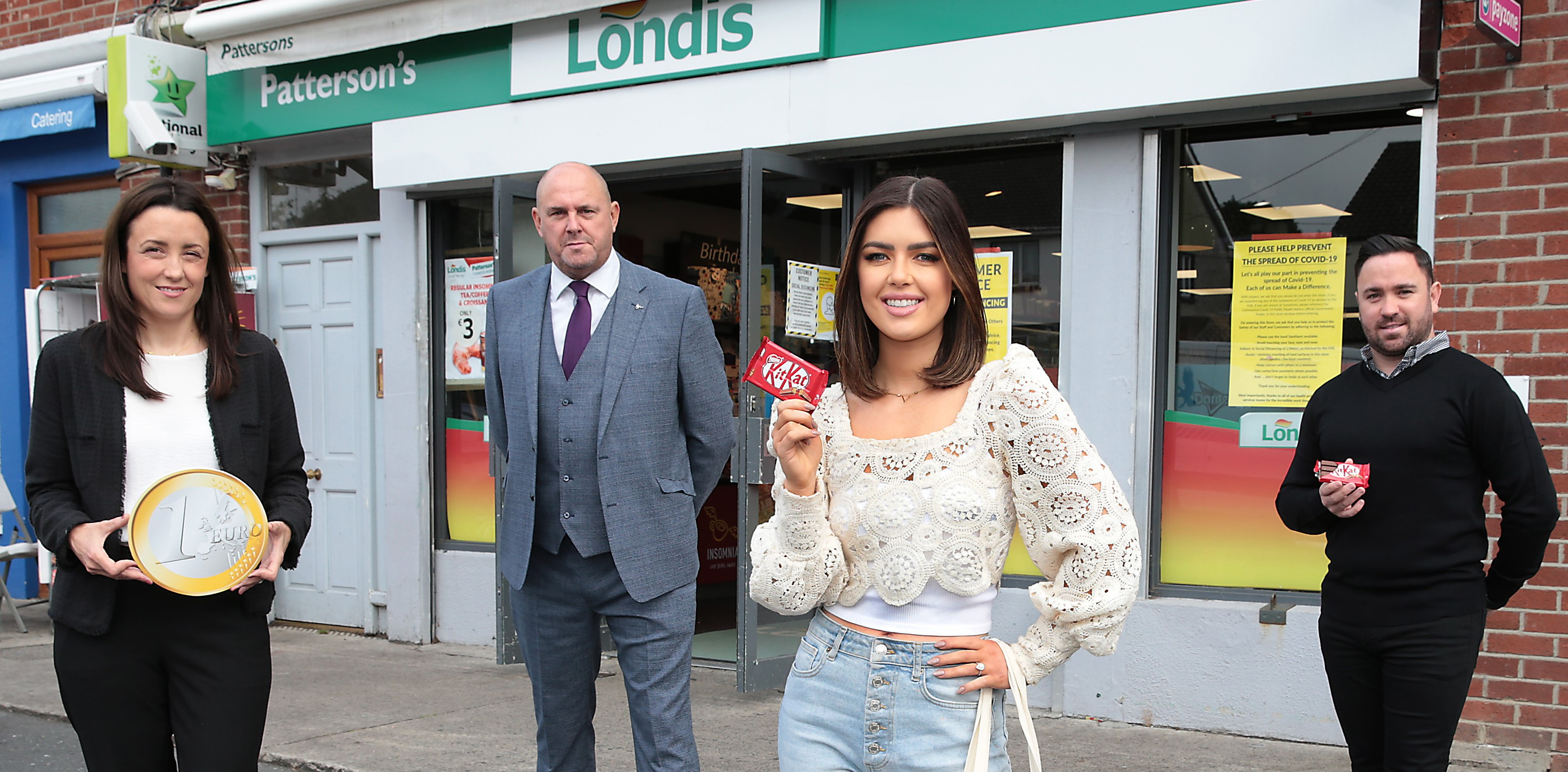 four people stood in front of a londis holding kitkats and a big euro