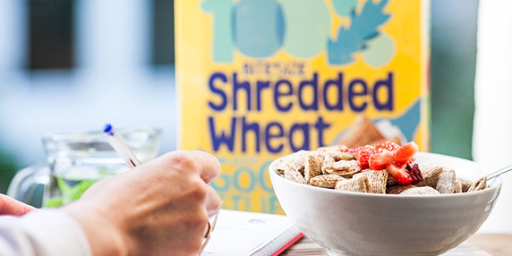 a bowl of shredded wheat woman's hand writing and shredded wheat box