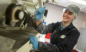 A lady in a hairnet, cap and blue gloves smiling and operating machinery