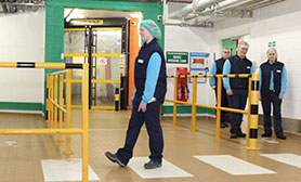 Employee in full PPC clothing walking across a crossing in the factory