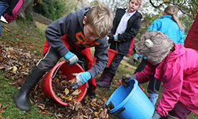 two children picking up leaves and putting them into buckets