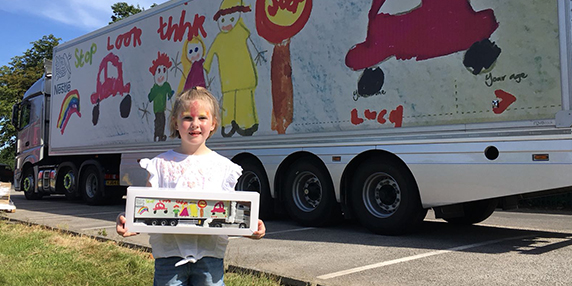 seven year old lucy pictured with prize in front of lorry after she won trailer design competition