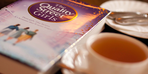 quality street girls book and cup of tea on the table