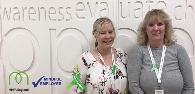 mental health awareness week two female employees wearing green ribbons